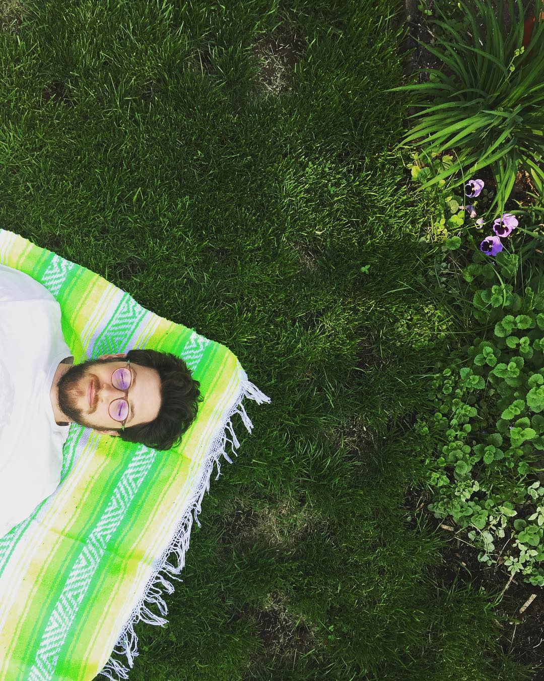 Jordan lying on a blanket in the grass